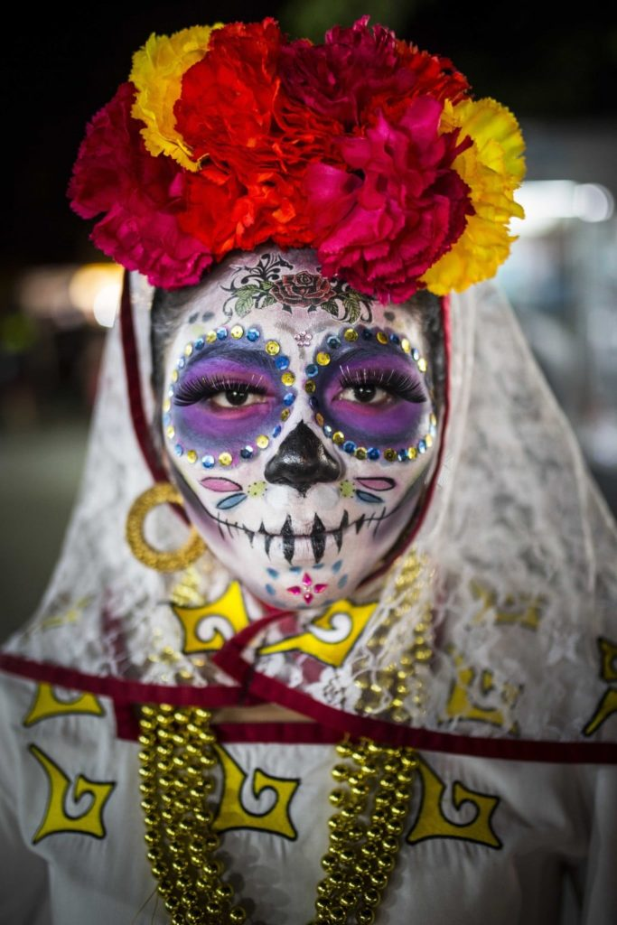 2 November 2016 - The portrait of a woman dressed in skull-candy face paint and costume to celebrate the Day of the Dead festival in Cancun's El Parque De Las Palapas, Mexico. The festival, locally known as 'Dia De Los Muertos' is an annual celebration in memory of loved ones who have passed away. Seeing the festival has been on my bucket-list for years, so when my trip to Mexico coincided with the celebrations I asked some locals where best to witness it. I spotted this woman just before leaving the festival, after all the parades and dancing had finished. Her eyes were so enchanting and her make-up pristine, I couldn't resist stopping her and asking for a photograph. I find her solemn expression juxtaposed with her colourful make up and accessories striking, and a nice portrayal of how the event celebrates what is usually considered a sad time.